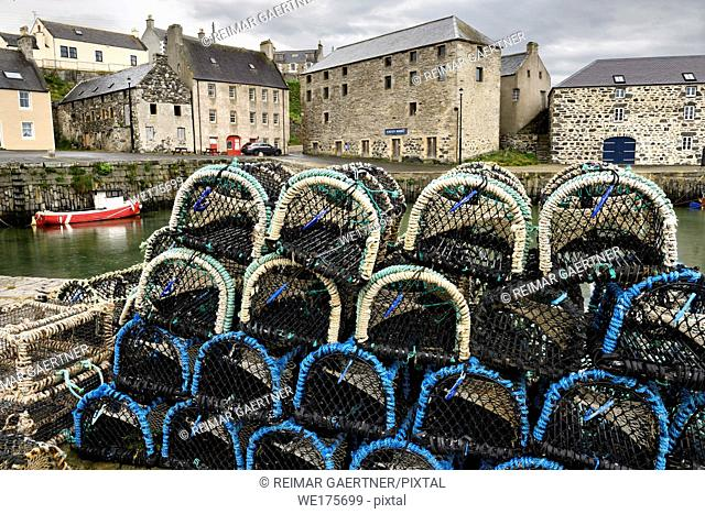 Lobster traps on stone dock of Old Harbourside Portsoy with stone Portsoy Marble warehouse Aberdeenshire Scotland UK