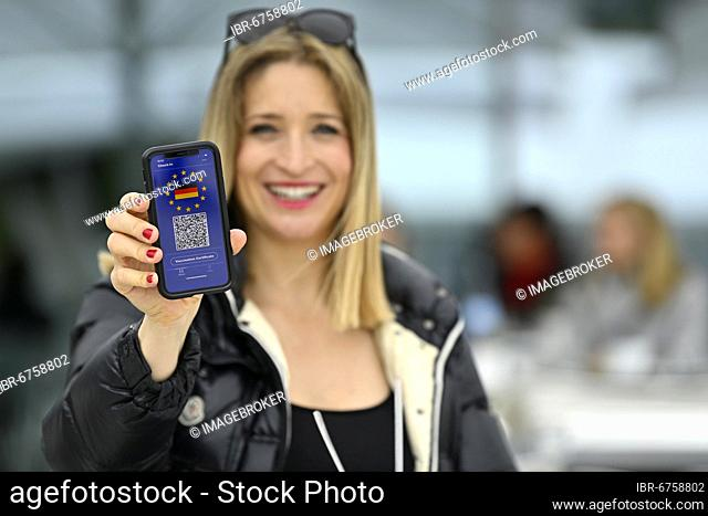 Symbol photo vaccination privilege, smiling woman shows smartphone with digital European vaccination certificate for German citizens, with QR code