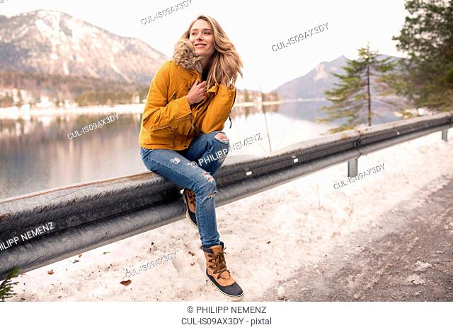 Portrait of mid adult woman sitting on railing by side of road, German Alps, Germany