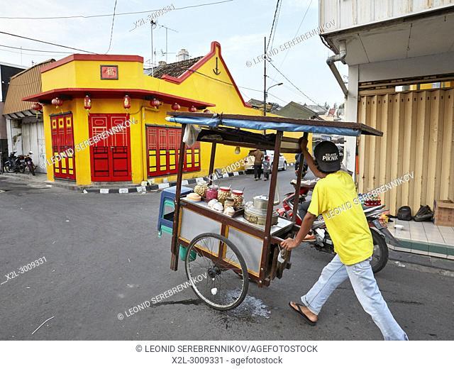 Street vendor pushing his mobile food stall along Ketandan Wetan street. Yogyakarta, Java, Indonesia