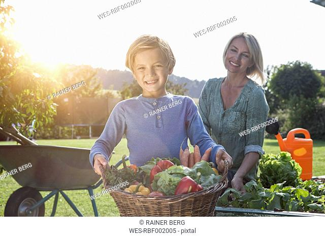 Boy with mother in garden carrying basket with vegetables