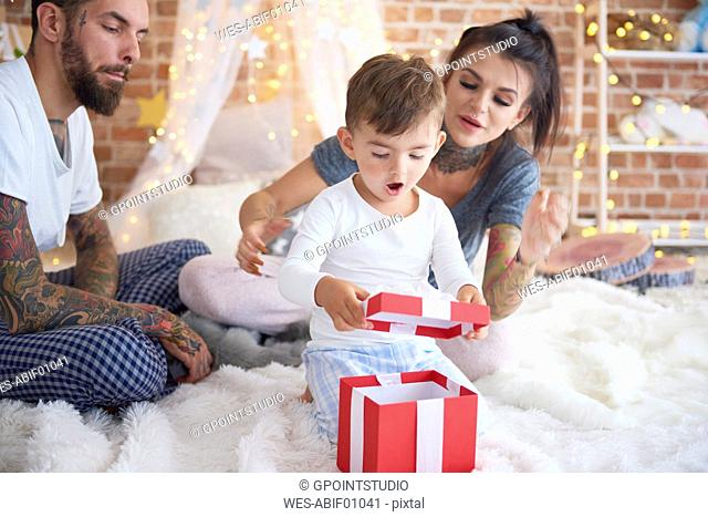 Surprised boy opening Christmas present with his parents in bed