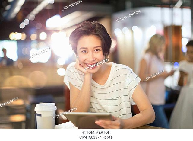Portrait smiling young woman using digital tablet and drinking coffee in cafe