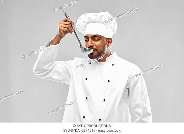 happy male indian chef tasting food from ladle