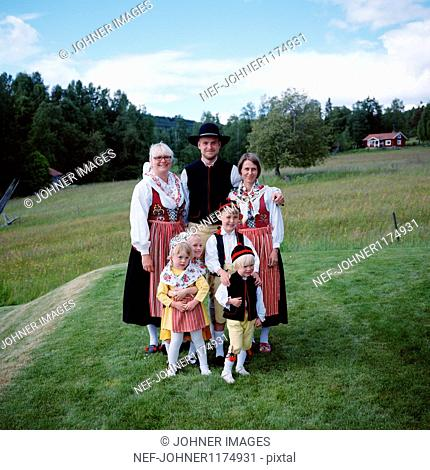 Family in traditional clothing standing on grass field, smiling