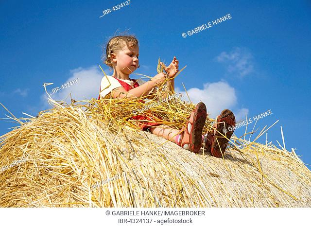 Little girl sitting on a straw bale under a cloudy blue sky, Germany