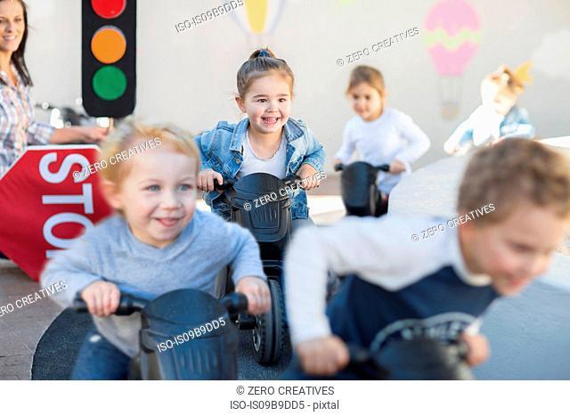 Boys and girls at preschool, racing push motorbikes in garden