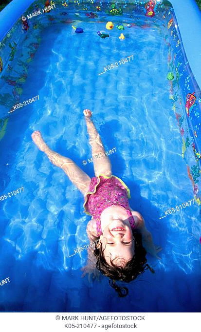 Girl (3yr) floating in an inflatable pool