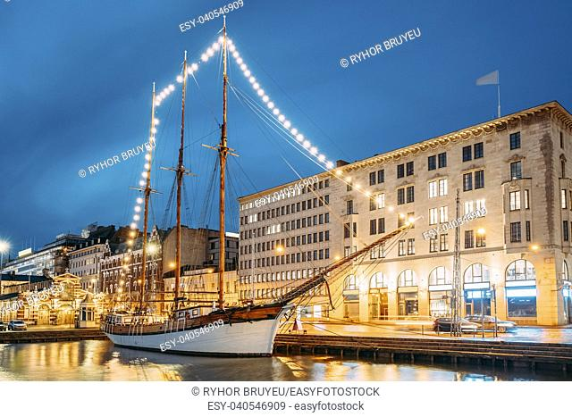 Helsinki, Finland. Old Wooden Sailing Vessel Ship Schooner Is Moored To The City Pier, Jetty. Unusual Cafe Restaurant In City Center In Lighting At Evening Or...