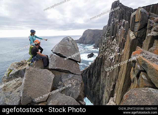 A male and a female rockclimber point at the next challenge they will tackle, scoping out possible ways up the sea cliffs of Cape Raoul, Tasmania, Australia
