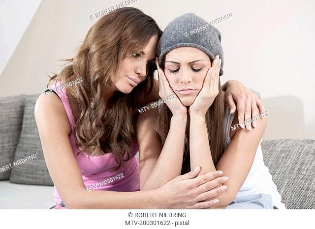 Young woman consoling her female friend