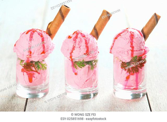 Three glasses strawberry ice cream in cup with waffle on wooden vintage table background