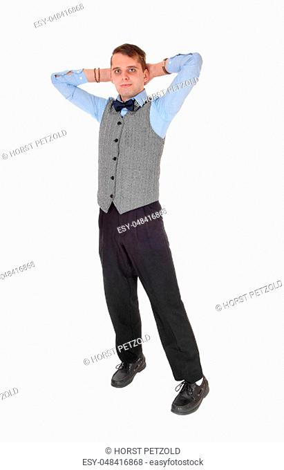 A young tall businessman standing in a gray vest and bow tie with his.hands behind his head, isolated for white background