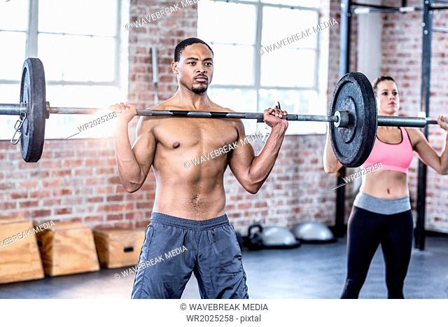 Fit couple lifting weight together