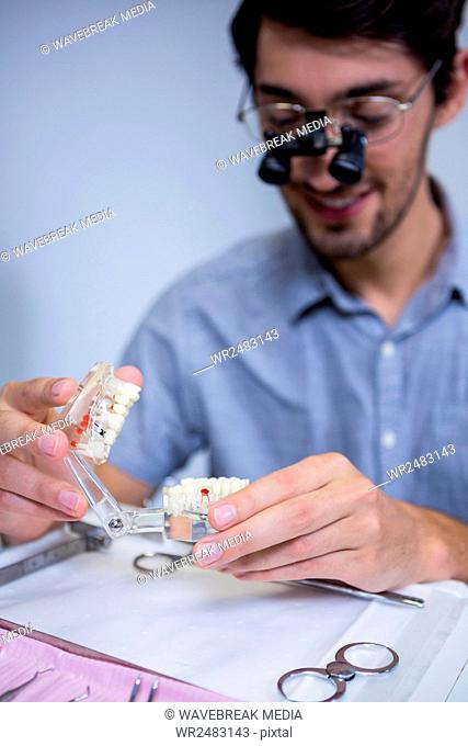 Male dentist looking at mouth model
