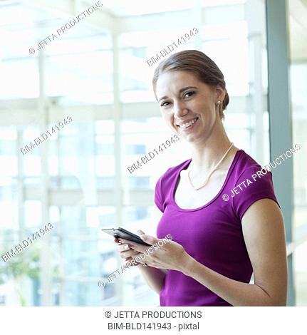 Caucasian businesswoman using cell phone in office