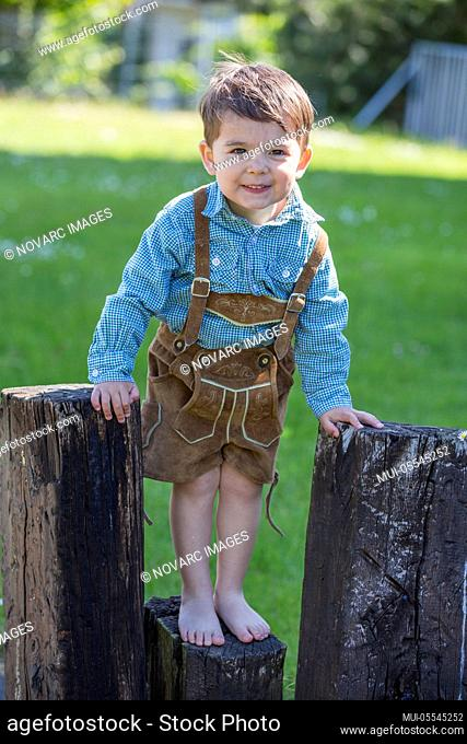 Little boy with leather pants climbs on wooden beams
