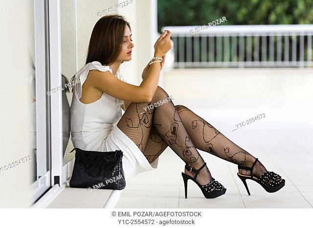 Young woman fashionable in White dress and fishnets