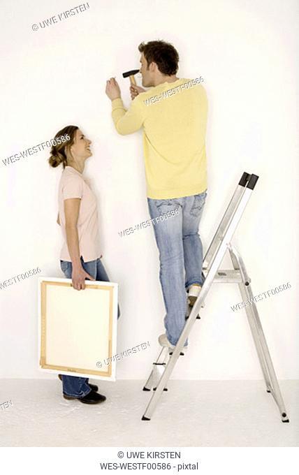 Young couple, man hammering nail into wall