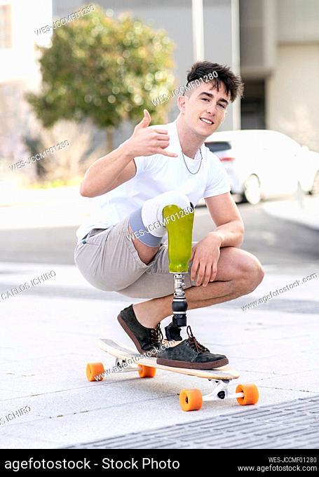 Smiling disabled man showing shaka sign while skateboarding on street