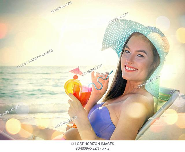 Portrait of young woman sitting on deckchair with cocktail at Miami beach, Florida, USA