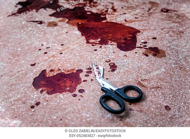 Trauma shears or bandage scissors lying on floor with stains of human blood around. Blood loss and bleeding stop, emergency medical aid for gunshot wounds