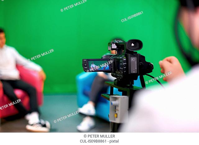 Young male and female college students practicing in TV studio with green screen