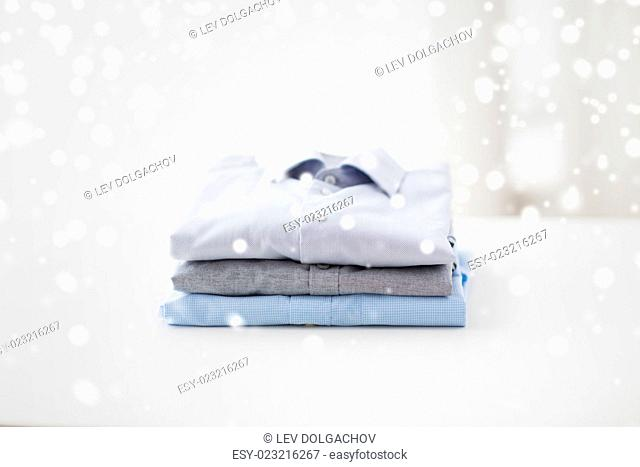 ironing, laundry, clothes, housekeeping and objects concept - close up of ironed and folded shirts on table at home over snow effect