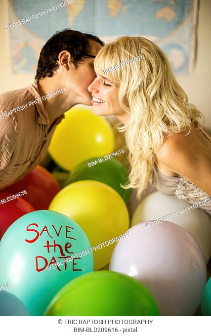 Caucasian couple kissing over balloon with 'save the date text