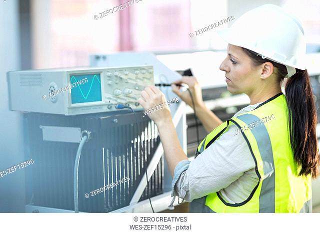 Female technician working on oscilloscope