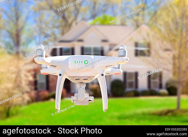 Back of Unmanned Aircraft System (UAV) Quadcopter Drone Flying In Front of House