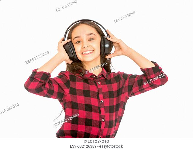 smiling dark-haired girl in a plaid shirt and jeans listening through large black headphones music putting forth the hand shows the gesture of Victoria
