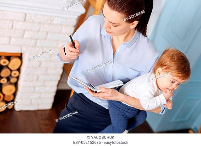 So many tasks. Enterprising hardworking young mother working on her schedule for the day while taking care of her child and making some notes