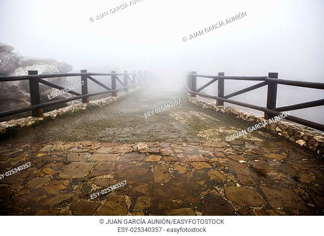 Wooden walkway lost in the fog. Torcal De Antequera, Malaga, Spain