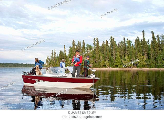 A family fishing from their motorboat on a calm lake in Northern Ontario; Ontario, Canada