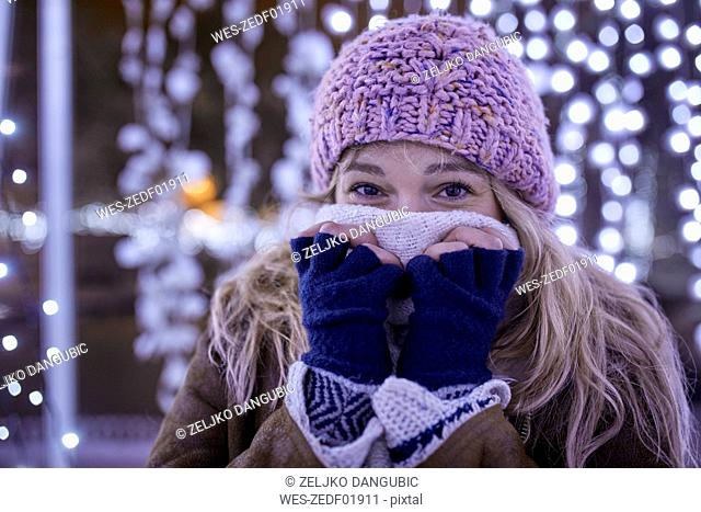 Portrait of young woman in winter clothes freezing