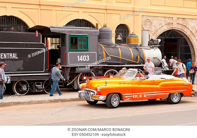 Havana Cuba february 2012 a typical Cuban cabriolet passes in front of the old steam train on display near the harbor in the afternoon in Havana Cuba