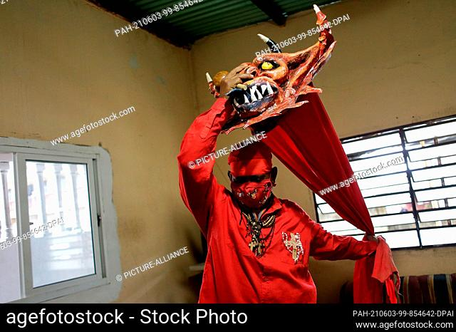 "03 June 2021, Venezuela, Yare: A man gets ready to dance during the folk festival """"Los Diablos Danzantes"""" (The Dancing Devils)"