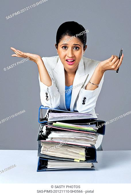 Businesswoman leaning on a stack of files and looking upset