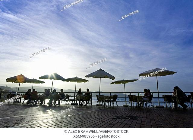Bar Parasols and People silhouetted against the sunny sky on the Las Canteras Beachfront in Las Palmas de Gran Canaria