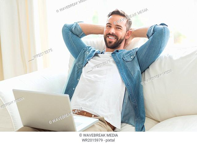 Smiling man resting in the sofa with laptop beside