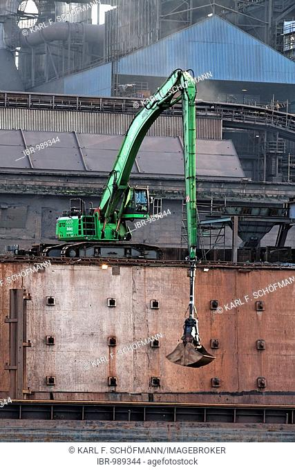 Modern mechanical digger, unloading in front of industrial setting, Krupp Mannesman smeltery, Rhine harbour, Duisburg, Ruhr area, North Rhine-Westphalia