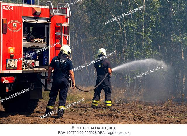 26 July 2019, Brandenburg, Jüterbog: Firefighters extinguish the forest fire at the former military training area near Jüterbog