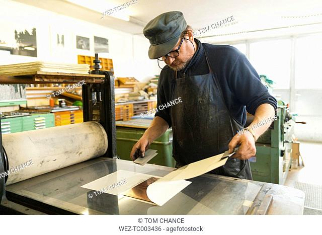 Germany, Bavaria, Mature man looking at deckle edge paper in print shop