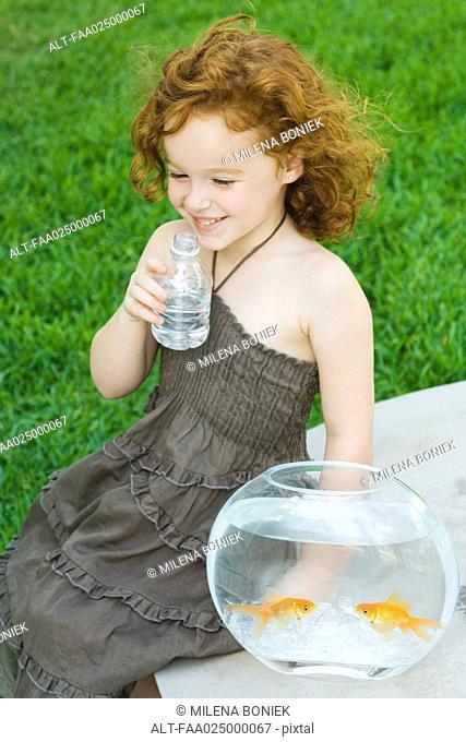 Girl sitting next to goldfish bowl, drinking water