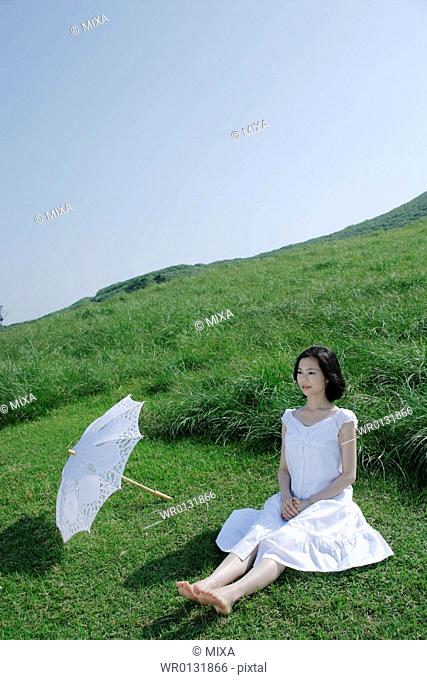 A young woman sitting on grass field