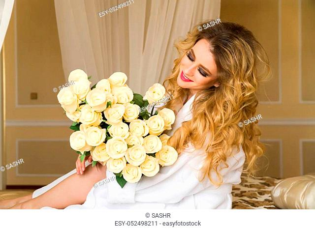 Beautiful seductive woman flirting with the camera is sitting on the bed with a big bouquet of white roses in White bathrobe looking up with a coquettish look