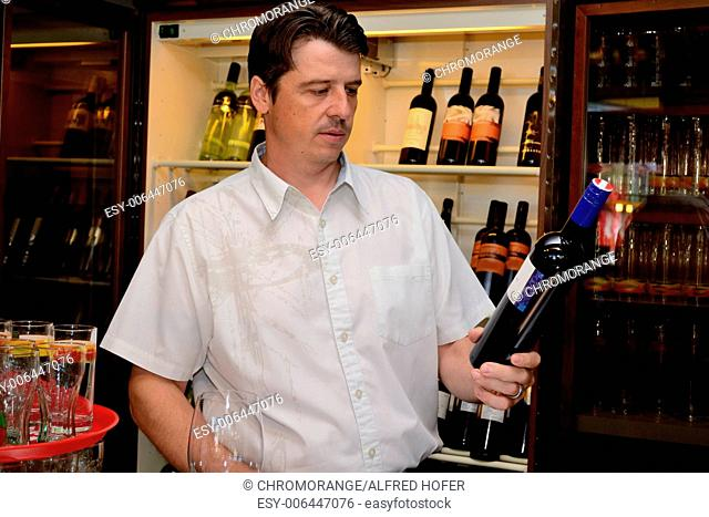 Hotelier with red wine bottle