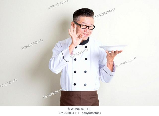 Mature Asian chef holding an empty plate, showing tasty and satisfied hand sign, standing on plain background