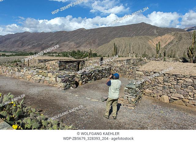 A tourist is videoing the houses of the pre-Inca fortress of Tilcara (Pucar
